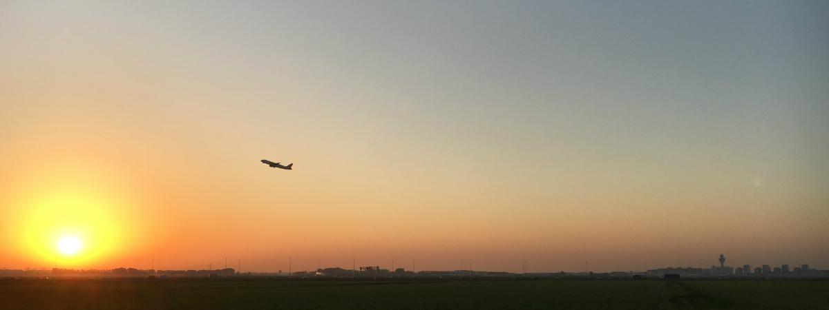 Opstijgend vliegtuig Schiphol bij zonsopgang